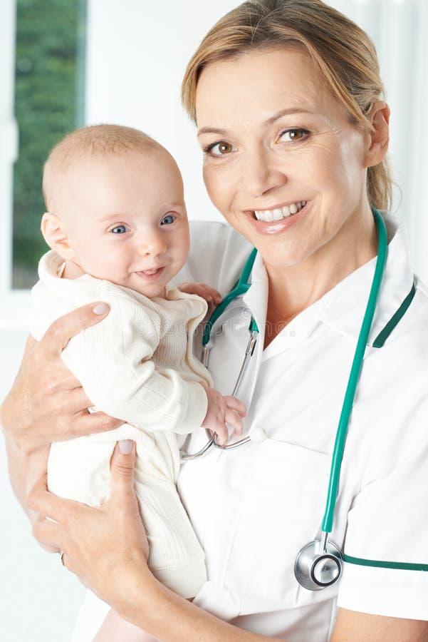 拿着女婴的护士画象 库存照片