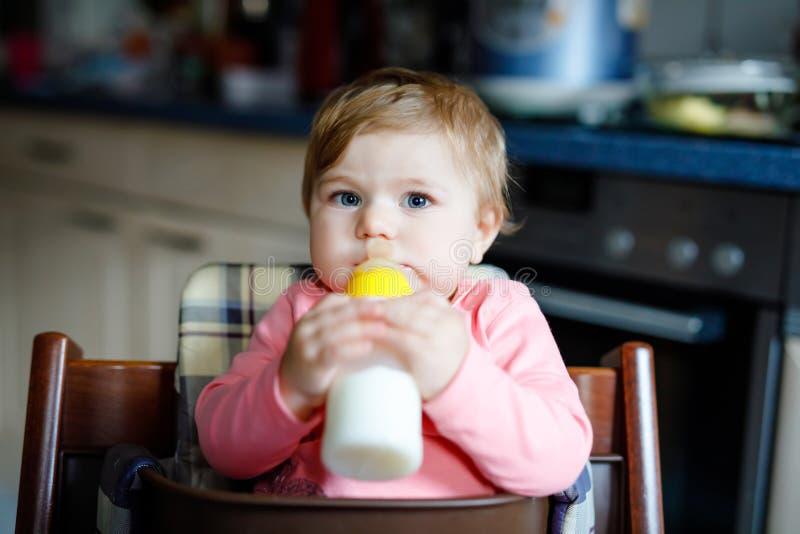 拿着奶瓶和喝惯例牛奶的逗人喜爱的可爱的女婴 婴孩的第一食物 婴儿,坐 库存照片