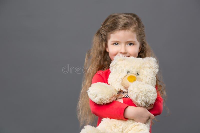 拿着她喜爱的玩具的快乐的逗人喜爱的女孩 免版税库存图片