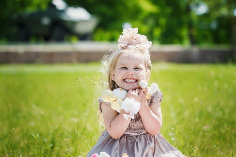 拿着她在summe的微笑的女孩画象喜爱的软的玩具 库存照片