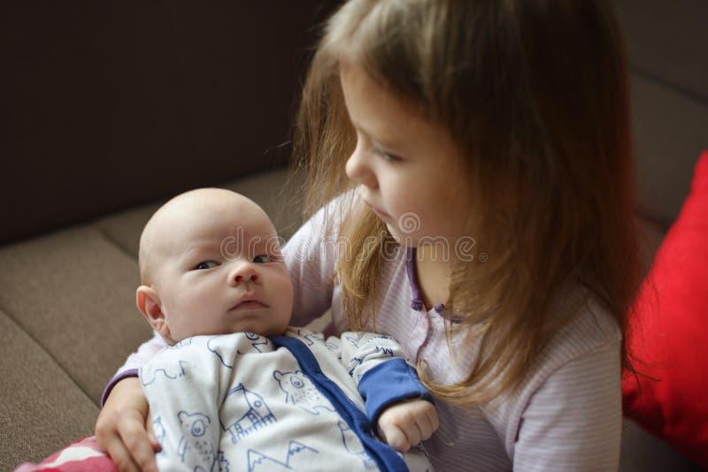 拿着她新出生的兄弟的姐妹 免版税库存照片