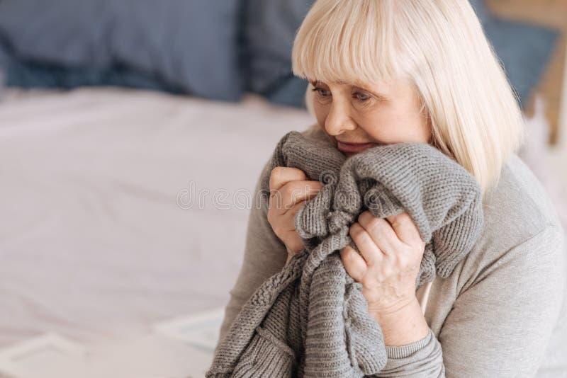 拿着她的丈夫的一件被编织的夹克沮丧的了无欢乐的妇女 库存图片