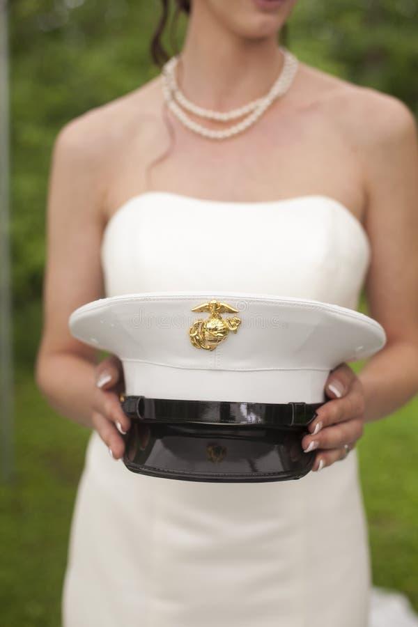 拿着她的丈夫的军队帽子的新娘 免版税图库摄影
