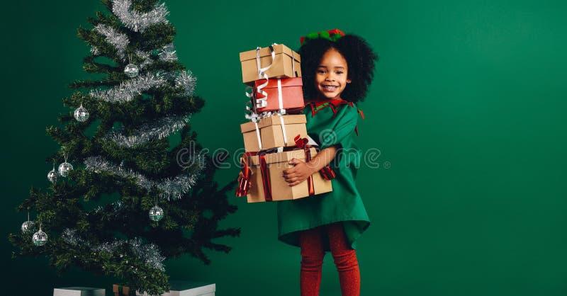 拿着她的圣诞礼物箱子的孩子站立在一棵装饰的圣诞树旁边 运载堆礼物的愉快的美国黑人的女孩 免版税库存图片