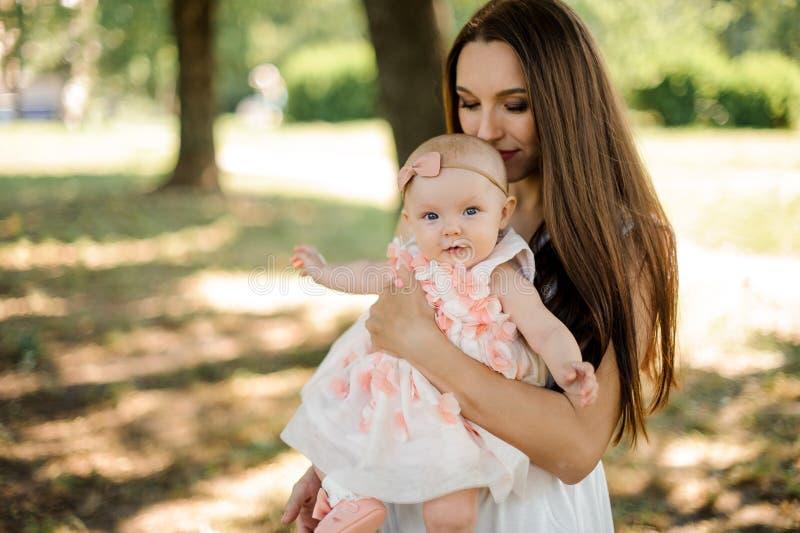 拿着她的在手上的愉快的母亲小逗人喜爱的女儿在pa 免版税图库摄影