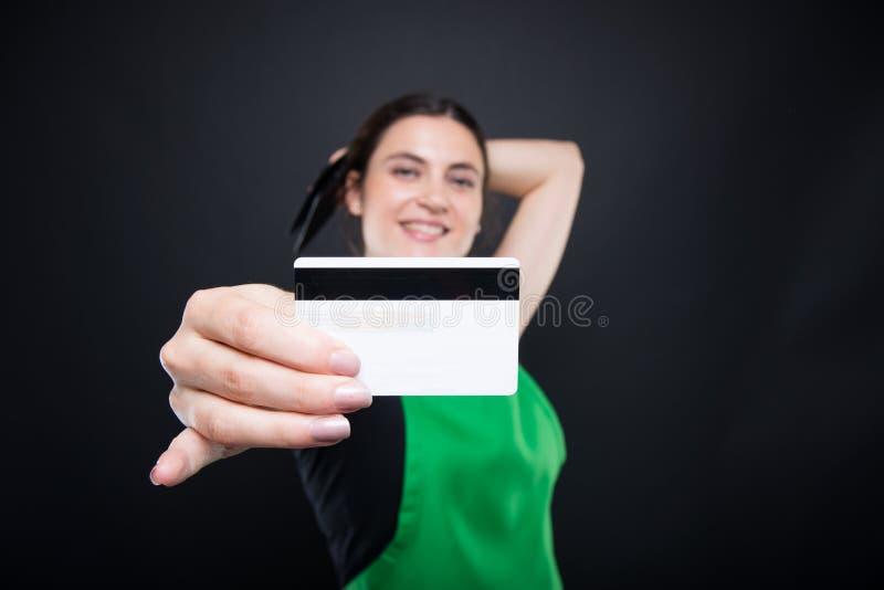拿着她的在特写镜头的超级市场卖主信用卡 库存照片