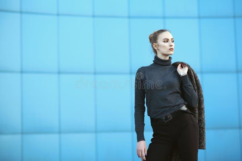 拿着她的在肩膀身分后的美丽的年轻女人夹克在城市购物中心前面蓝色墙壁  免版税图库摄影