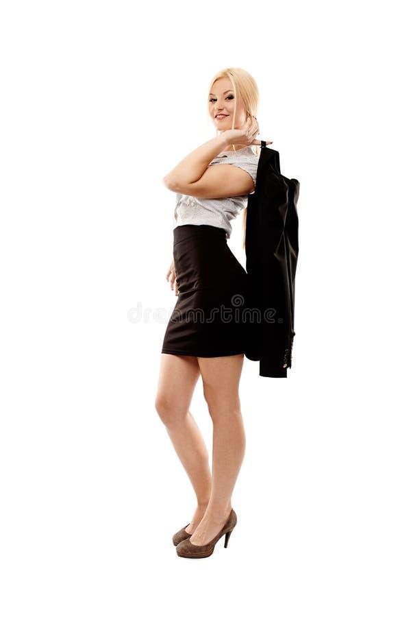 拿着她的外套的轻松的女实业家 免版税库存图片