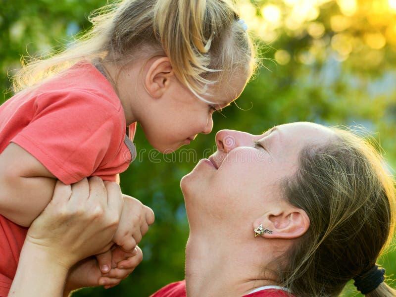 拿着她的女儿的少妇面对面 库存图片