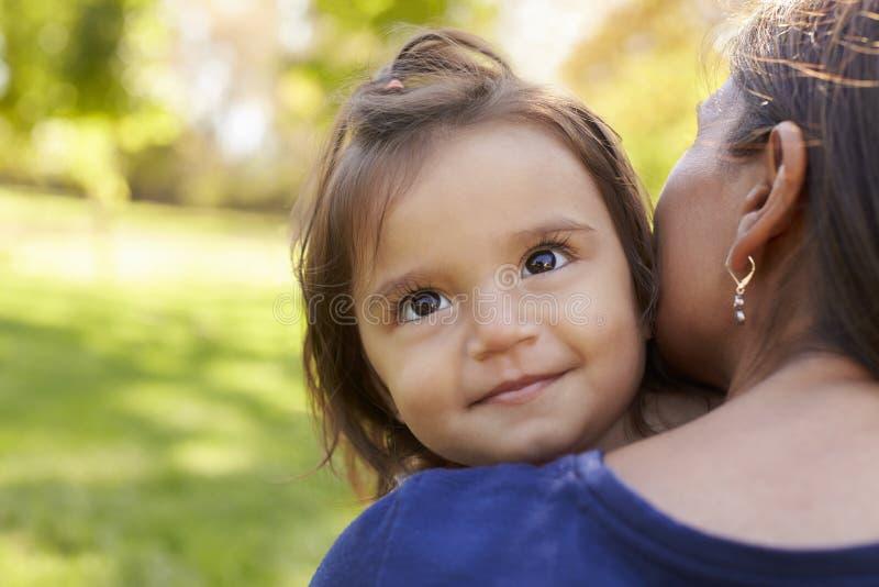 拿着她的女儿,在肩膀视图的混合的族种母亲 免版税库存照片