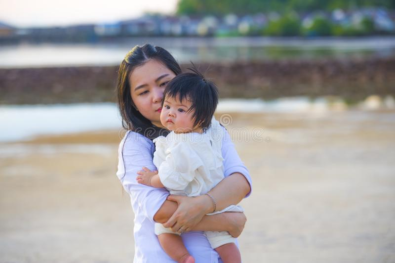 拿着她的她的胳膊的可爱的女婴的年轻愉快的亚裔中国妇女母亲甜矮小的女儿散步在 图库摄影