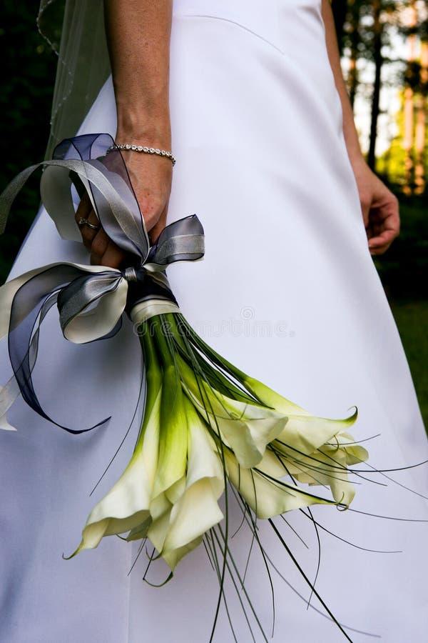 拿着她的婚礼花束的新娘由她的边 免版税库存照片