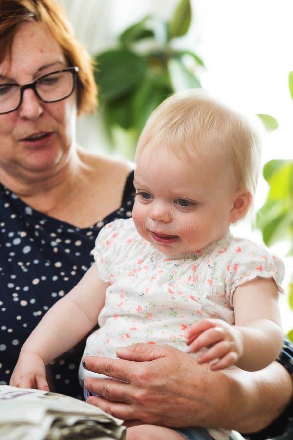 拿着她的孙,幸福家庭的祖母 图库摄影