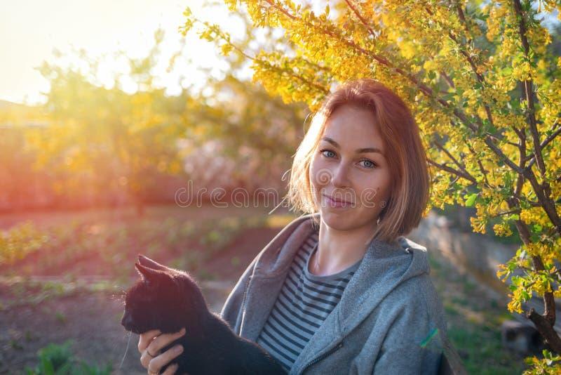 拿着她的宠物猫的年轻俏丽的妇女 在背景的日落 免版税库存图片