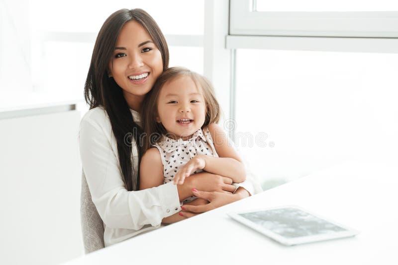 拿着她的小女儿的愉快的微笑的亚裔妈妈 库存图片