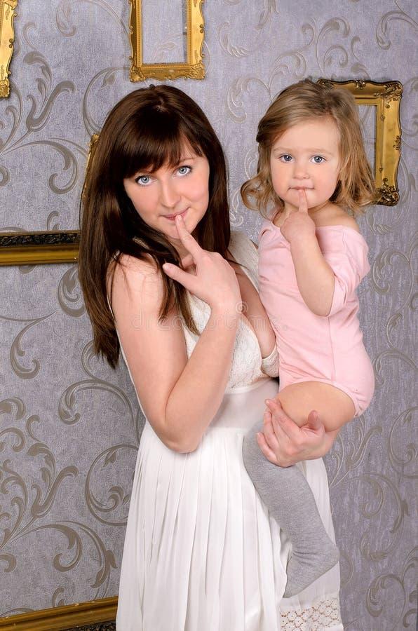 拿着她的小女儿的滑稽的妈妈 库存图片