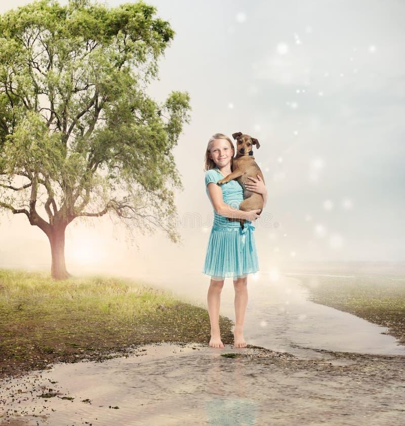 拿着她的小狗的女孩在一条魔术溪 库存图片
