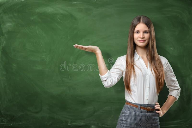 拿着她的开放棕榈和显示在绿色黑板的空的区域的美丽的少妇在她后 免版税库存照片