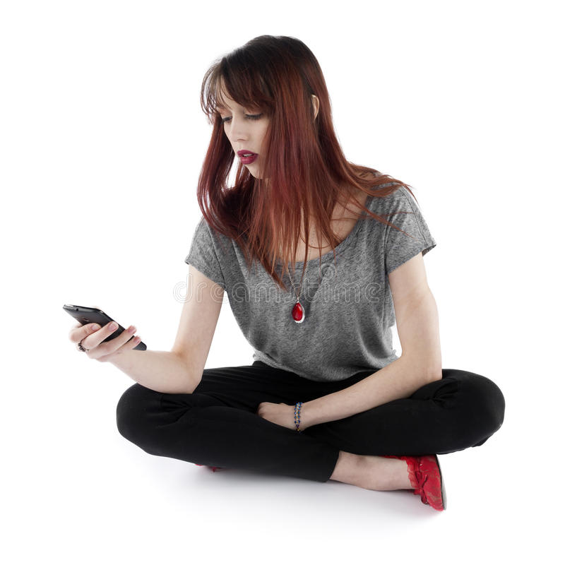 拿着她的手机的坐的俏丽的妇女 库存图片