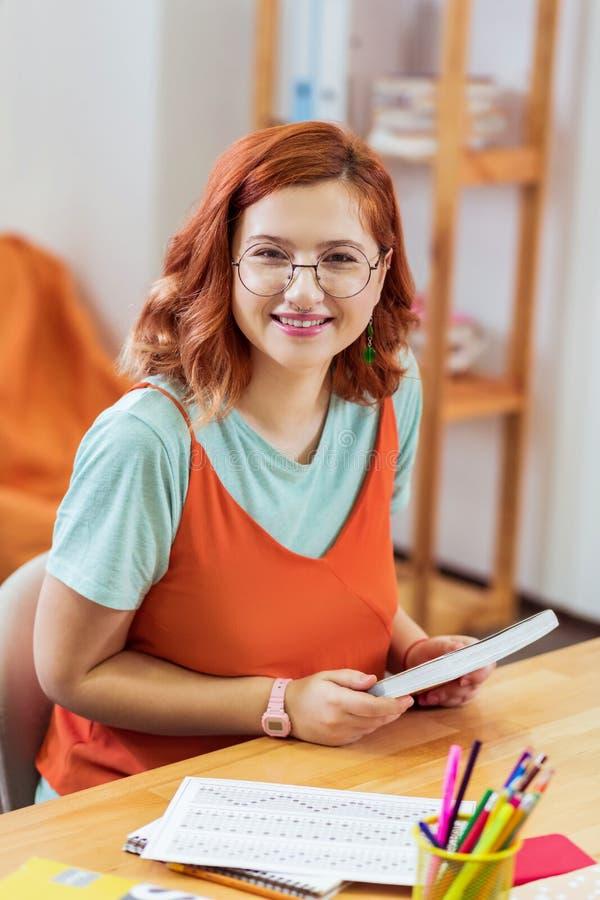 拿着她的指南的高兴聪明的年轻女人 库存照片