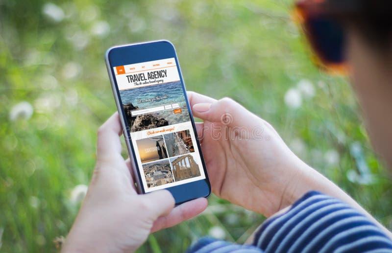 拿着她的有旅行社的草的女孩智能手机 库存照片