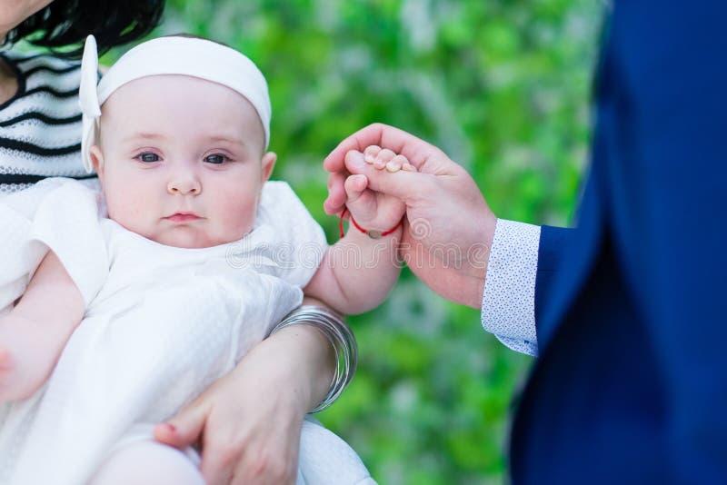 拿着她的爸爸手画象的女婴 库存图片