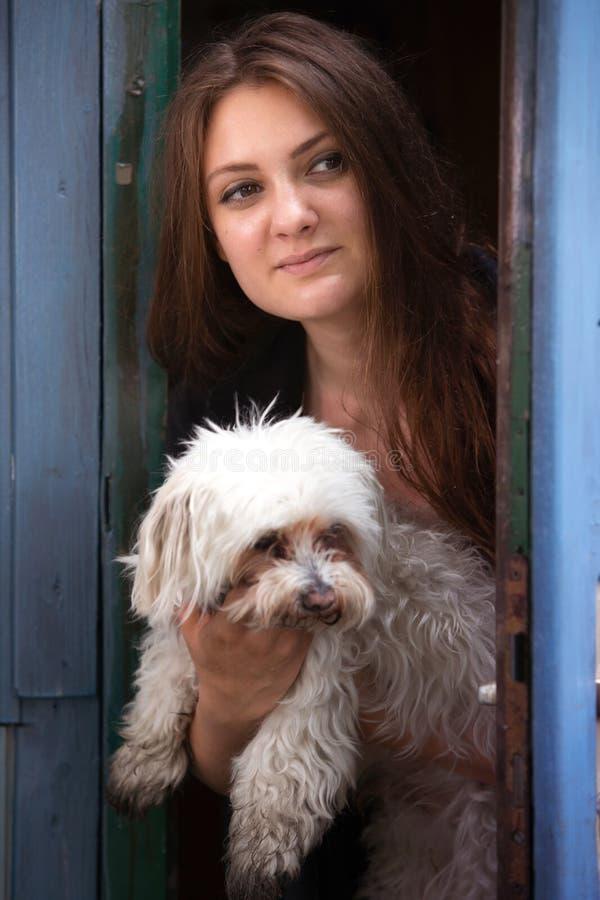 拿着她的狗和站立在蓝色门的年轻女人 库存图片