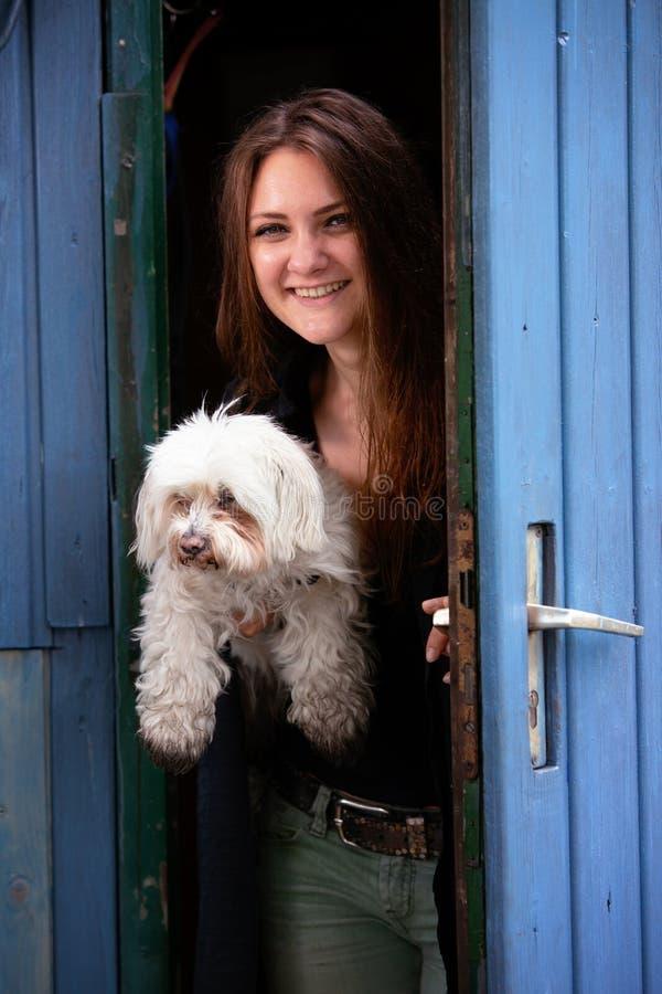 拿着她的狗和站立在蓝色门的年轻女人 库存照片