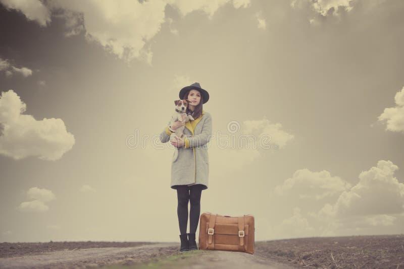 拿着她的狗的美丽的少妇在wonde的手提箱附近 免版税库存照片