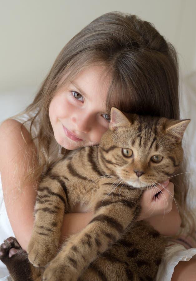 拿着她的猫的小女孩画象 免版税库存照片