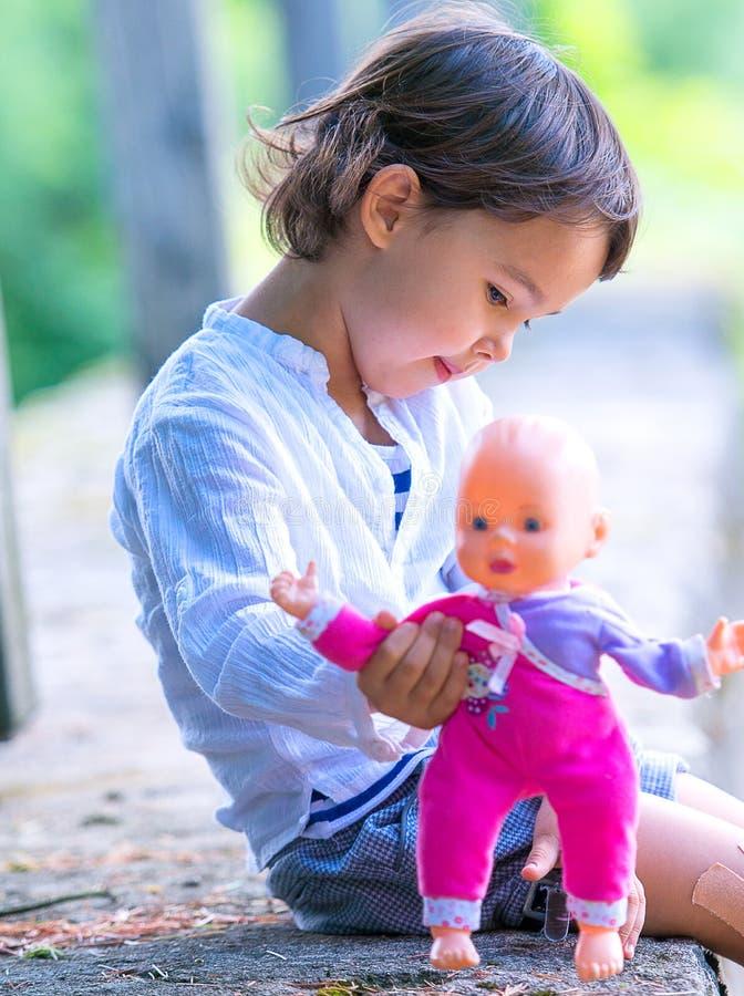 拿着她的玩偶的逗人喜爱的小女孩 库存图片