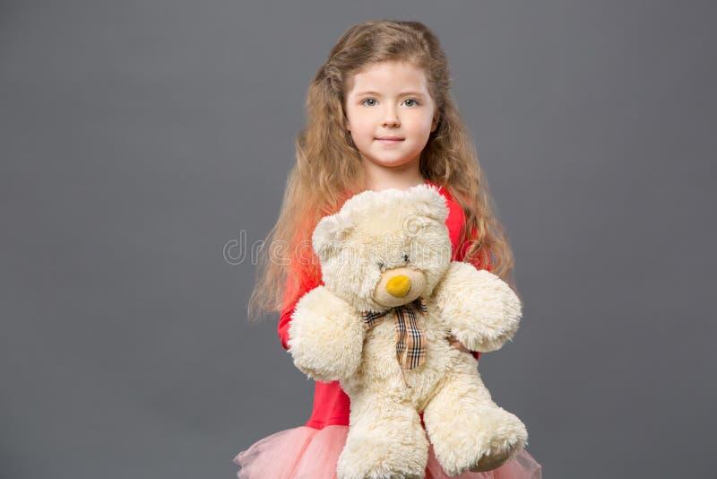 拿着她的玩具的宜人的好女孩 库存照片