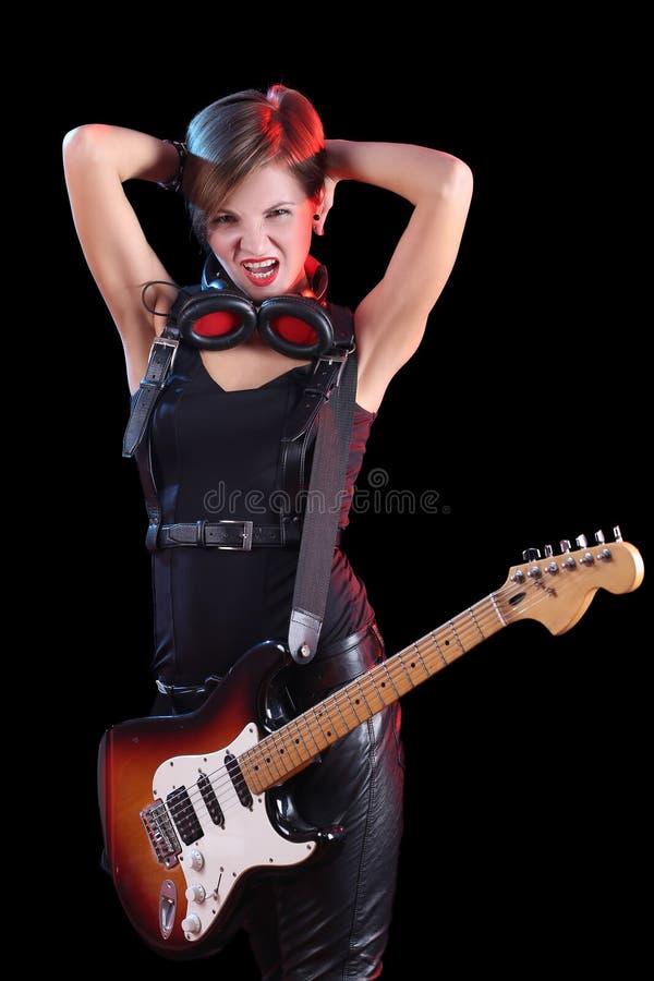 拿着她的电吉他的摇滚明星 性感的女孩 库存照片
