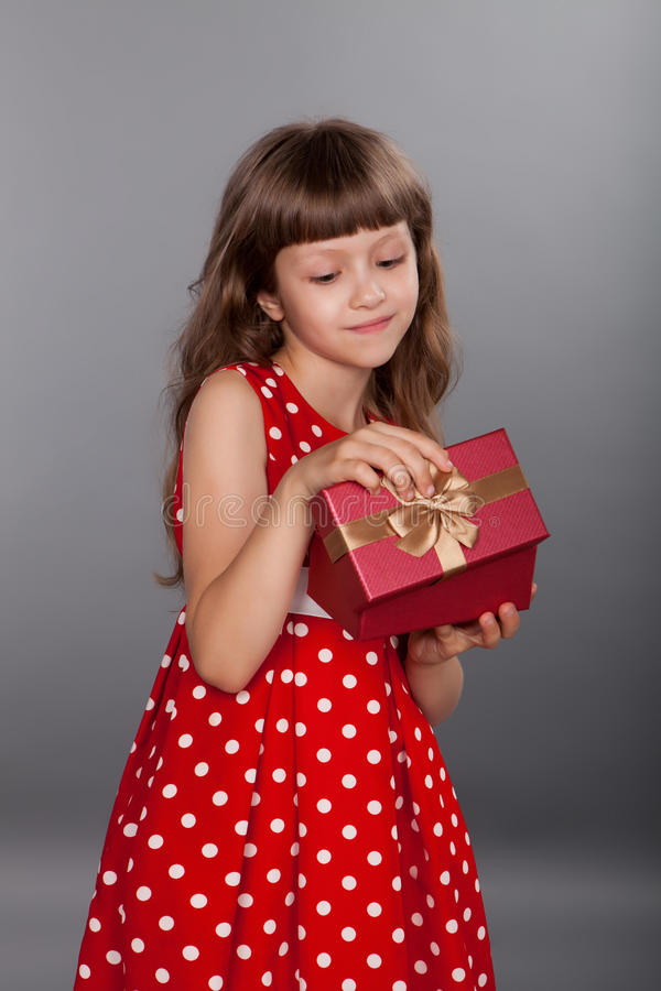 拿着她的礼物的红色礼服的小女孩 库存图片