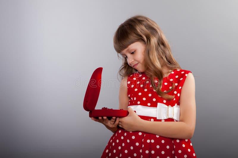 拿着她的礼物的红色礼服的小女孩 库存照片