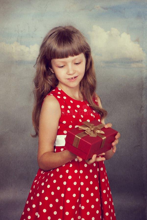 拿着她的礼物的红色礼服的小女孩 免版税库存图片