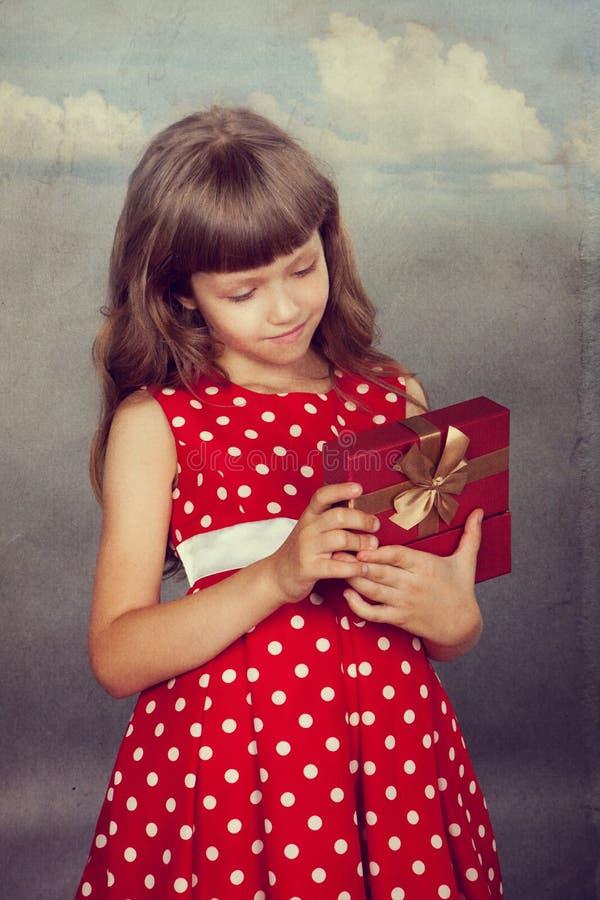 拿着她的礼物的红色礼服的小女孩 图库摄影