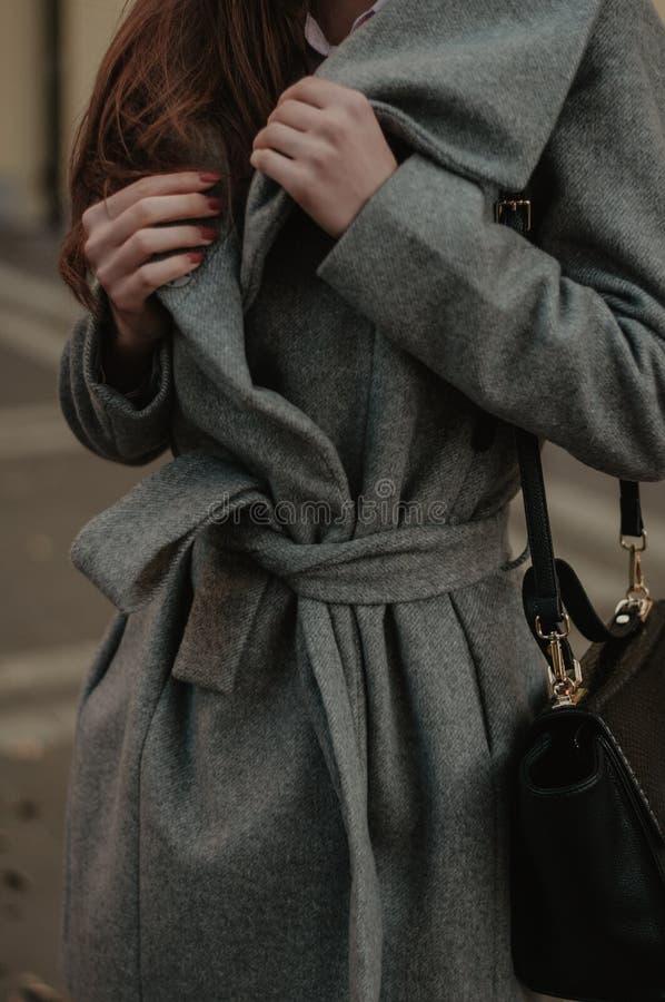 拿着她的秋天外套特写镜头的妇女 库存照片