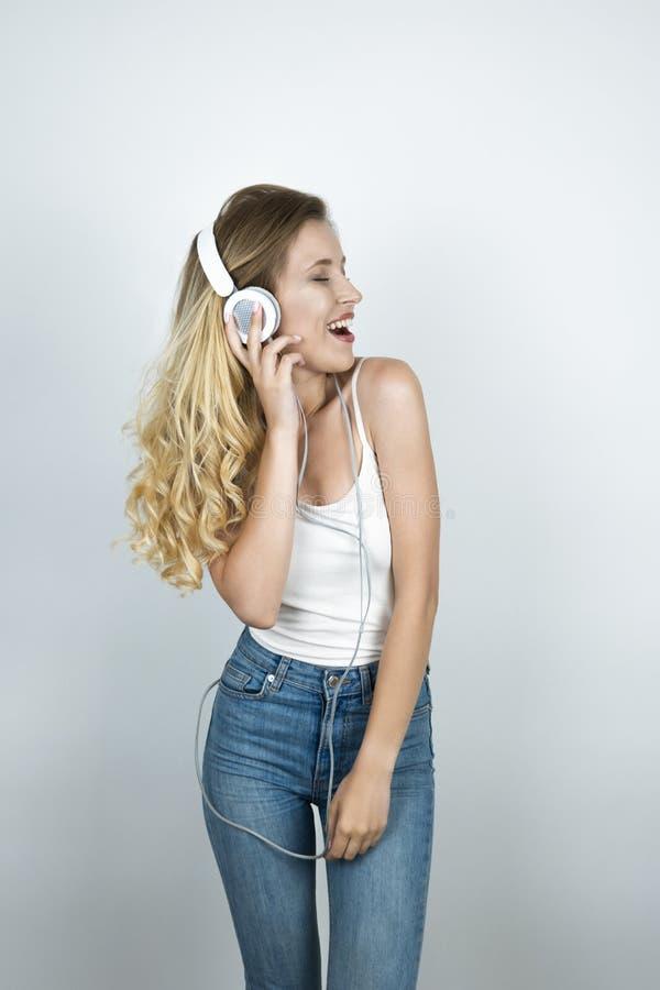 拿着她的耳机单手的白肤金发的妇女听音乐微笑的白色背景 免版税库存照片