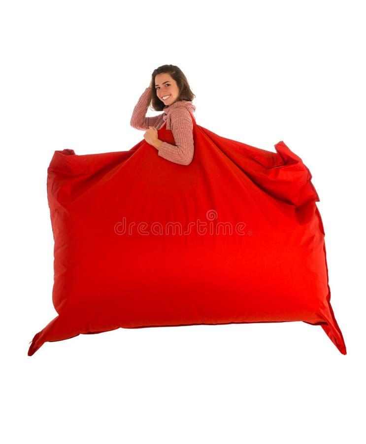 拿着她的肩膀红色长方形shap的年轻微笑的妇女 免版税库存图片
