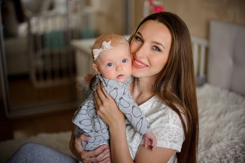 拿着她的胳膊的俏丽的妇女一个新出生的女婴 库存图片