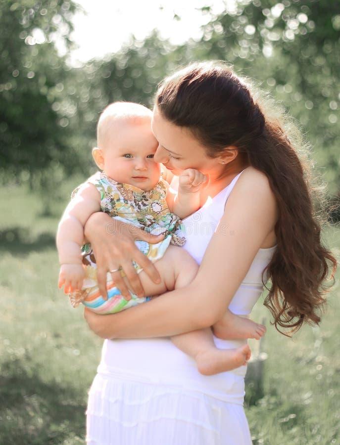 拿着她的胳膊的微笑的母亲小女儿,谈话,看有爱和崇拜的婴孩 库存照片