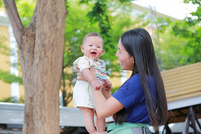 拿着她的胳膊的愉快的亚裔母亲婴儿在绿色庭院 免版税图库摄影
