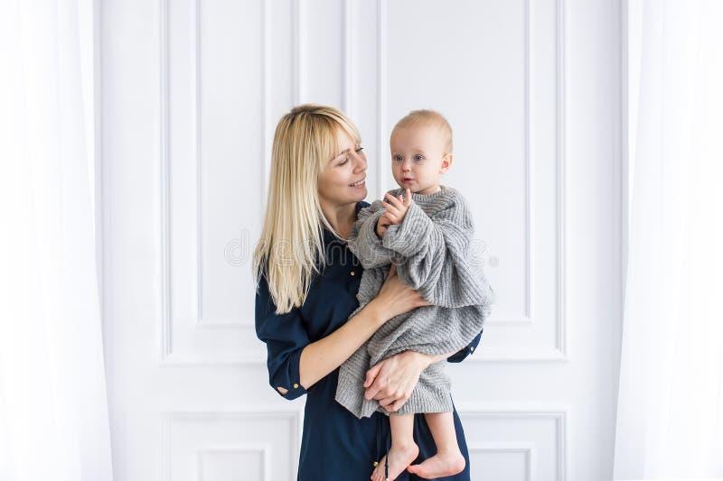 拿着她的胳膊的美丽的年轻母亲画象可爱的矮小的女婴 图库摄影