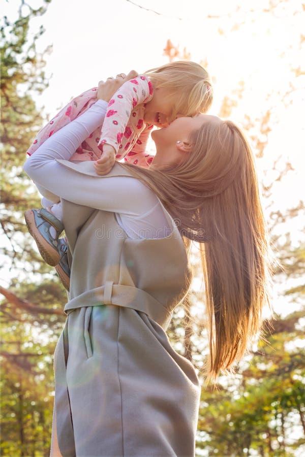 拿着她的胳膊的逗人喜爱的小孩女孩女儿和举她悬而未决,两个的年轻母亲笑 库存图片