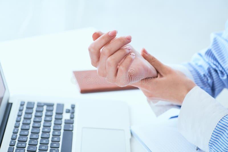 拿着她的腕子特写镜头的年轻女人 从使用计算机的痛苦 办公室综合症状由职业病的手痛苦 免版税库存图片