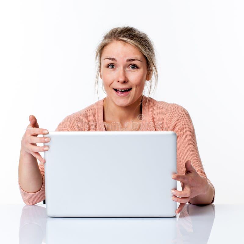 拿着她的膝上型计算机的笑的美丽的年轻白肤金发的女商人 免版税库存图片