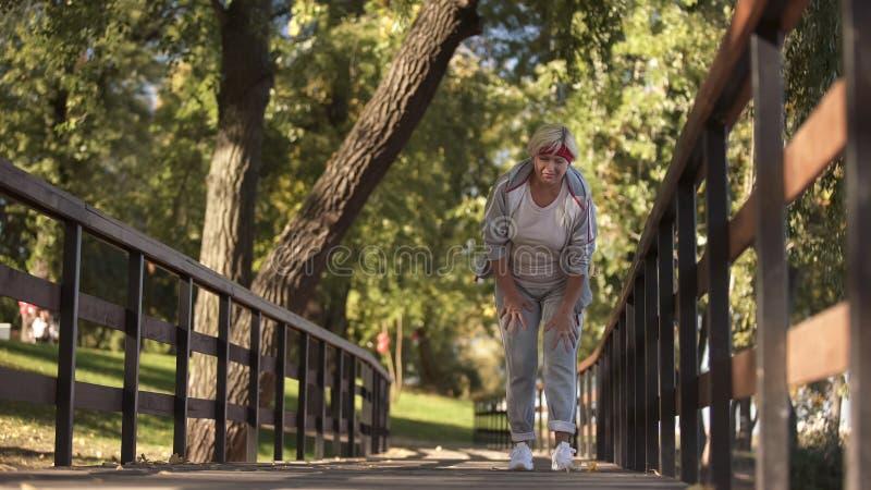 拿着她的膝盖的嬉戏资深夫人感觉锐痛在跑步期间,健康 库存图片