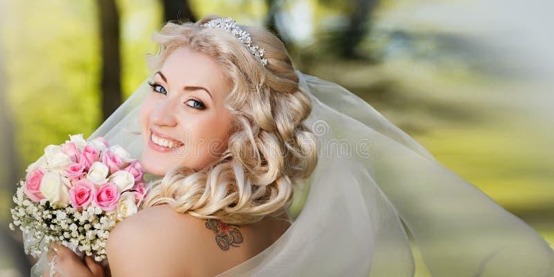 拿着她的花束的面纱的愉快的新娘看照相机在乡下 库存照片