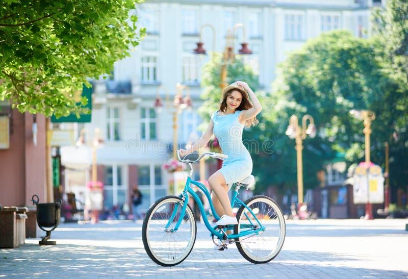 拿着她的草帽的可爱的妇女,当乘坐的蓝色自行车下来在夏日时铺了市中心 库存照片